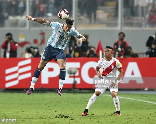 Marcos Rojo of Argentina heads the ball while observed by Christian Cueva of Peru during a match between Peru and Argentina as part of FIFA 2018...