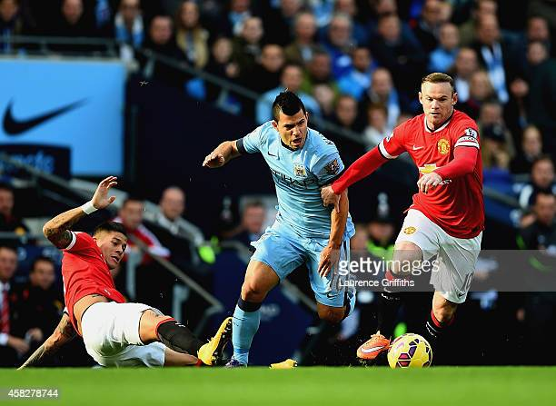 Marcos Rojo of Manchester United slides in as Sergio Aguero of Manchester City and Wayne Rooney of Manchester United battle for the ball as during...