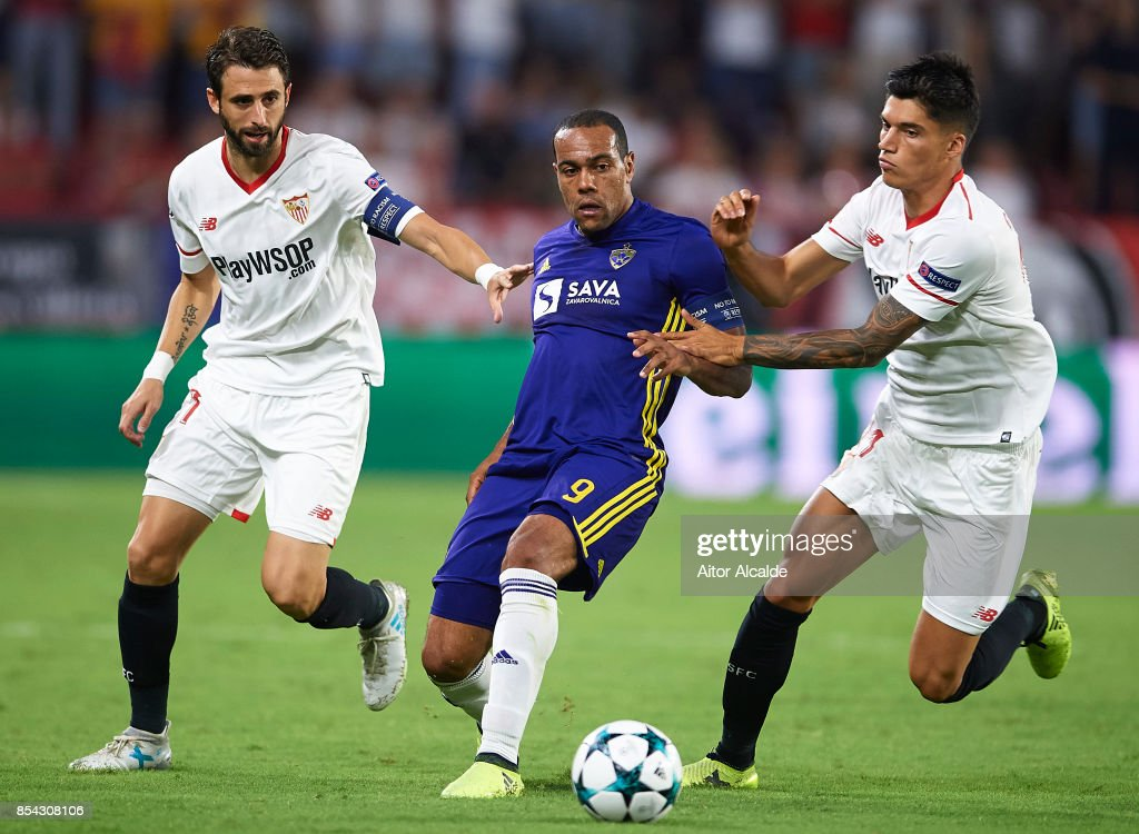 Marcos Tavares of NK Maribor (C) competes with Nicolas Pareja of Sevilla FC (L) and Joaquin Correa of Sevilla FC (R) during the UEFA Champions League match between Sevilla FC and NK Maribor at Estadio Ramon Sanchez Pizjuan on September 26, 2017 in Seville, Spain.