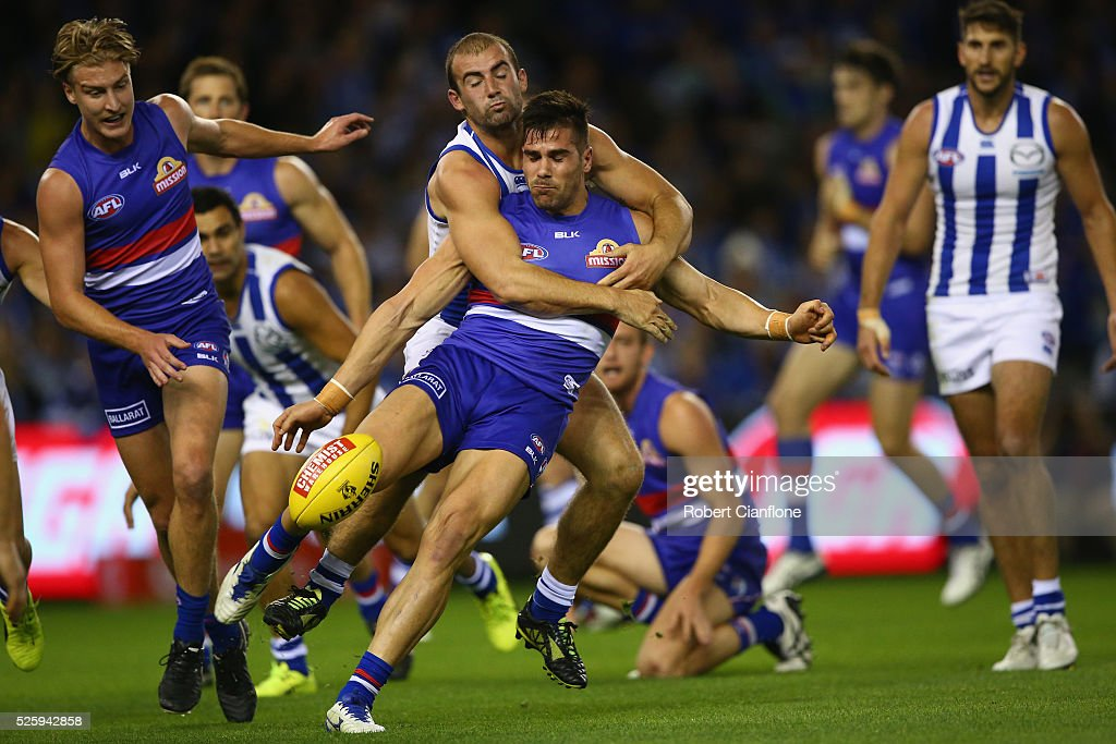 Marcus Adams of the Bulldogs is tackled by Ben Cunnington of the Kangaroos during the round six AFL match between the North Melbourne Kangaroos and the Western Bulldogs at Etihad Stadium on April 29, 2016 in Melbourne, Australia.