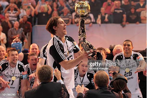 Marcus Ahlm of Kiel lifst up the handball champions trophy after winning 3634 the handball final match between THW Kiel and FC Barcelona Borges at...