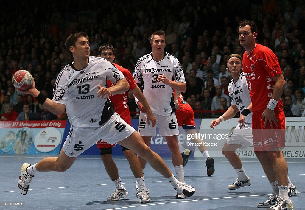<a gi-track='captionPersonalityLinkClicked' href=/galleries/search?phrase=Marcus+Ahlm&family=editorial&specificpeople=626527 ng-click='$event.stopPropagation()'>Marcus Ahlm</a> of Kiel (L) scores a goal against Jens Schoengarth of Melsungen (R) during the Toyota Handball Bundesliga match between MT Melsungen and THW Kiel at the Rotehnbach Hall on September 28, 2010 in Kassel, Germany.