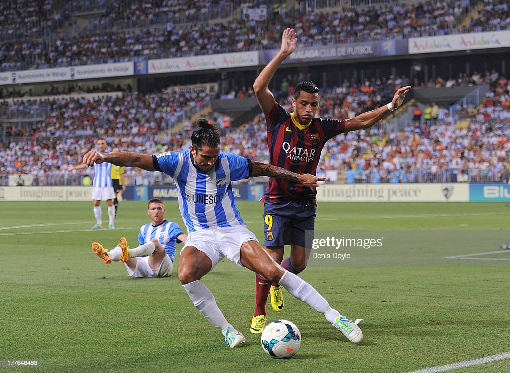 Marcus Angeleri (L) of Malaga CF clears the ball beside <a gi-track='captionPersonalityLinkClicked' href=/galleries/search?phrase=Adriano+-+Soccer+Defender+and+Midfielder+-+Born+1984&family=editorial&specificpeople=640788 ng-click='$event.stopPropagation()'>Adriano</a> Correia of FC Barcelona during the La Liga match between Malaga CF and FC Barcelona at La Rosaleda Stadium on August 25, 2013 in Malaga, Spain.