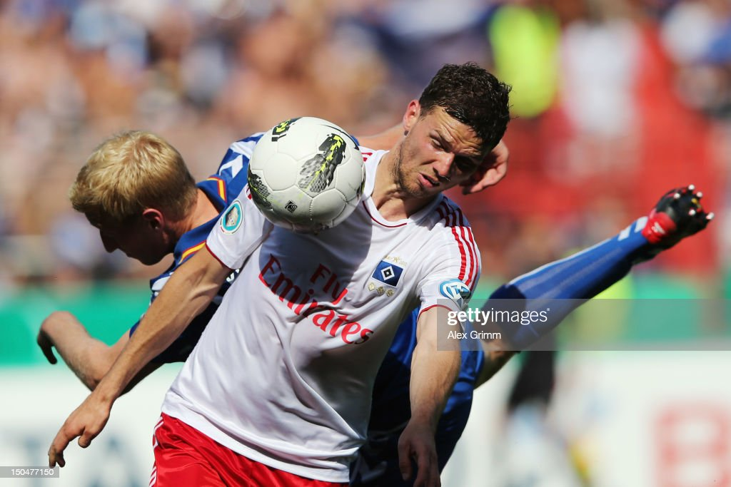 Marcus Berg (front) of Hamburg is challenged by Philipp Klingmann of Karlsruhe during the first round match of the DFB Cup between Karlsruher SC and Hamburger SV at Wildpark Stadium on August 19, 2012 in Karlsruhe, Germany.