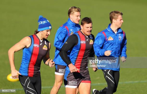 Marcus Bontempelli of the Bulldogs and Jack Redpath of the Bulldogs run during a Western Bulldogs AFL training session at Whitten Oval on June 23...