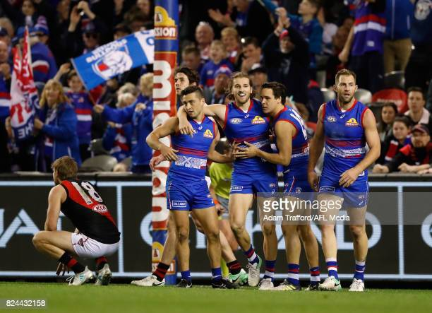 Marcus Bontempelli of the Bulldogs celebrates a goal with teammates during the 2017 AFL round 19 match between the Western Bulldogs and the Essendon...