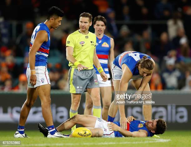 Marcus Bontempelli of the Bulldogs checks onTom Liberatore of the Bulldogs as he lays on the ground injured after a heavy tackle from Shane Mumford...
