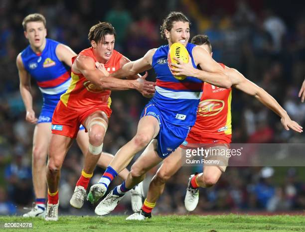 Marcus Bontempelli of the Bulldogs fends off a tackle by David Swallow of the Suns during the round 18 AFL match between the Western Bulldogs and the...