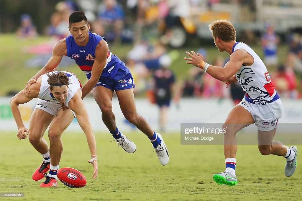 Marcus Bontempelli of the Bulldogs is tackled by Lin Jong of the Bulldogs as Mitch Wallis of the Bulldogs calls for the ball to be tapped during the Western Bulldogs AFL intra-club match at Whitten Oval on February 13, 2016 in Melbourne, Australia.