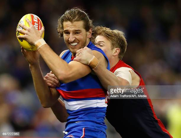 Marcus Bontempelli of the Bulldogs is tackled by Mitch Hannan of the Demons during the 2017 AFL round 13 match between the Western Bulldogs and the...