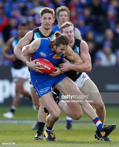 Marcus Bontempelli of the Bulldogs is tackled by Tom Jonas of the Power during the 2017 AFL round 22 match between the Western Bulldogs and the Port...