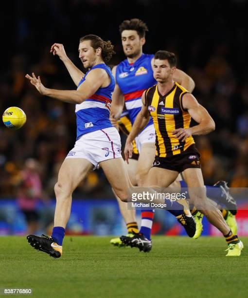 Marcus Bontempelli of the Bulldogs kicks the ball from Jaeger O'Meara of the Hawks during round 23 AFL match between the Hawthorn Hawks and the...