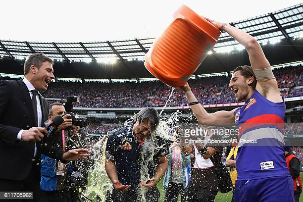 Marcus Bontempelli of the Bulldogs pours Gatorade on Bulldogs coach Luke Beveridge after winning the 2016 Toyota AFL Grand Final match between the...