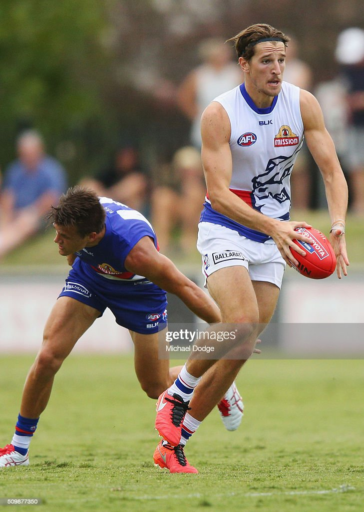 Marcus Bontempelli of the Bulldogs runs with the ball away from Jed Adcock during the Western Bulldogs AFL intra-club match at Whitten Oval on February 13, 2016 in Melbourne, Australia.