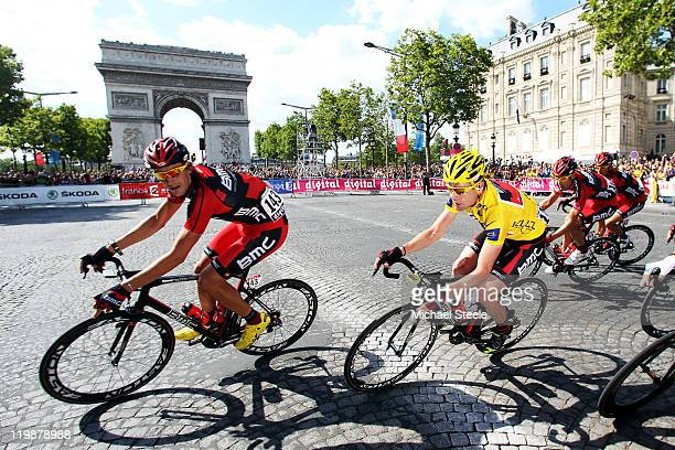 Marcus Burghardt of Team BMC leads teammate Cadel Evans through the corner during the twenty first and final stage of Le Tour de France 2011 from...