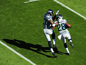 Marcus Burley of the Seattle Seahawks is congratulated by Tharold Simon after intercepting a pass against the Carolina Panthers on October 26 2014 at...