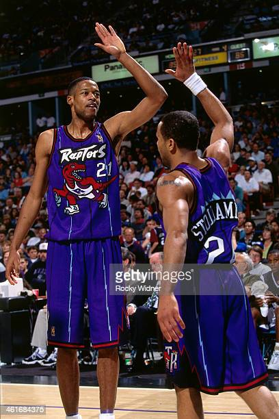 Marcus Camby and Damon Stoudamire of the Toronto Raptors high five each other during a game played on March 3 1997 at Arco Arena in Sacramento...