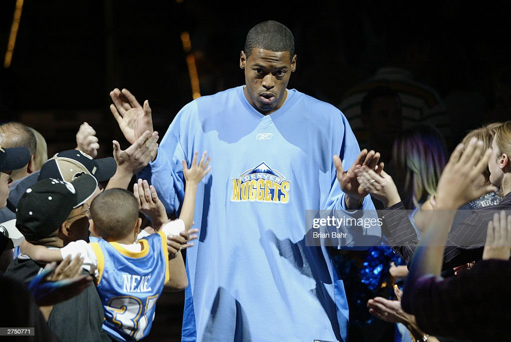 Marcus Camby #23 of the Denver Nuggets gets 'high-fives' from fans during player introductions prior to the game against the San Antonio Spurs on October 29, 2003 at the Pepsi Center in Denver, Colorado. The Nuggets won 80-72.