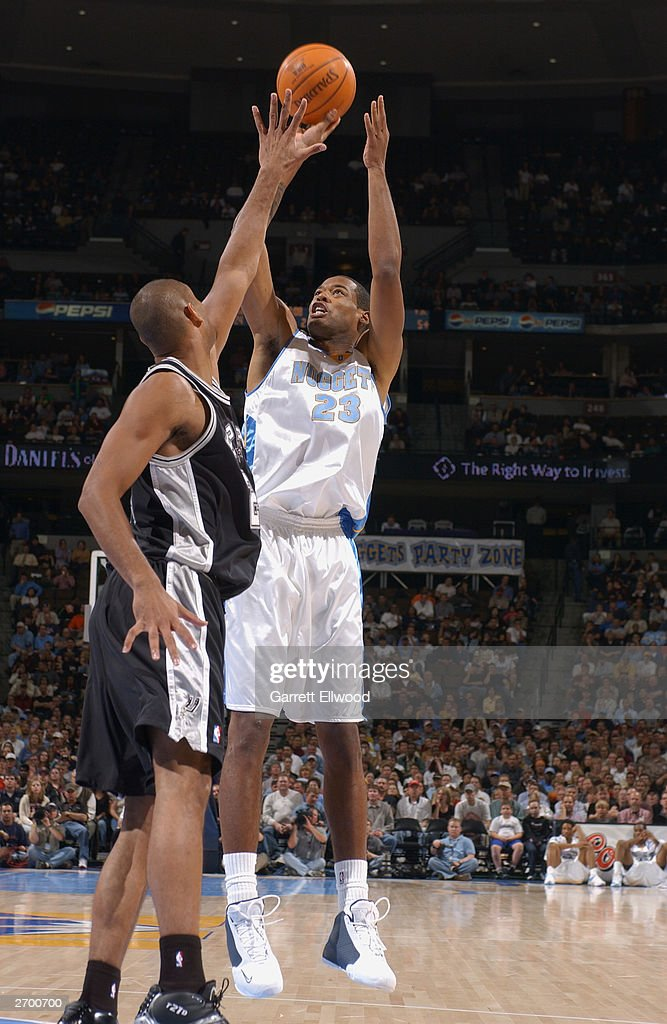 Marcus Camby #23 of the Denver Nuggets shoots over <a gi-track='captionPersonalityLinkClicked' href=/galleries/search?phrase=Tim+Duncan&family=editorial&specificpeople=201467 ng-click='$event.stopPropagation()'>Tim Duncan</a> #21 of the San Antonio Spurs at the Pepsi Center on October 29, 2003 in Denver, Colorado. The Nuggets won 80-72.