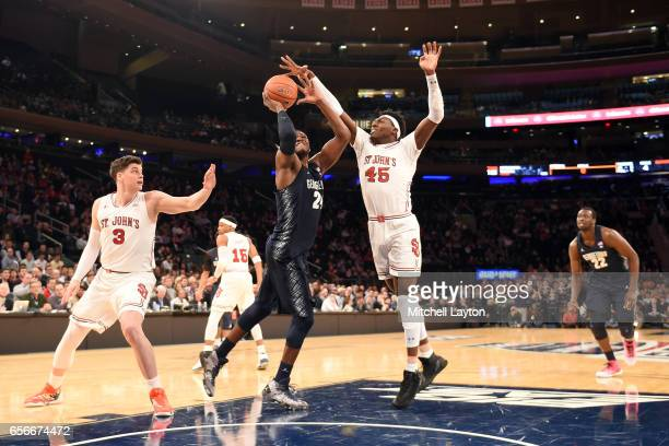 Marcus Derrickson of the Georgetown Hoyas takes a shot over Darien Williams of the St John's Red Storm during the Big East Basketball Tournament...