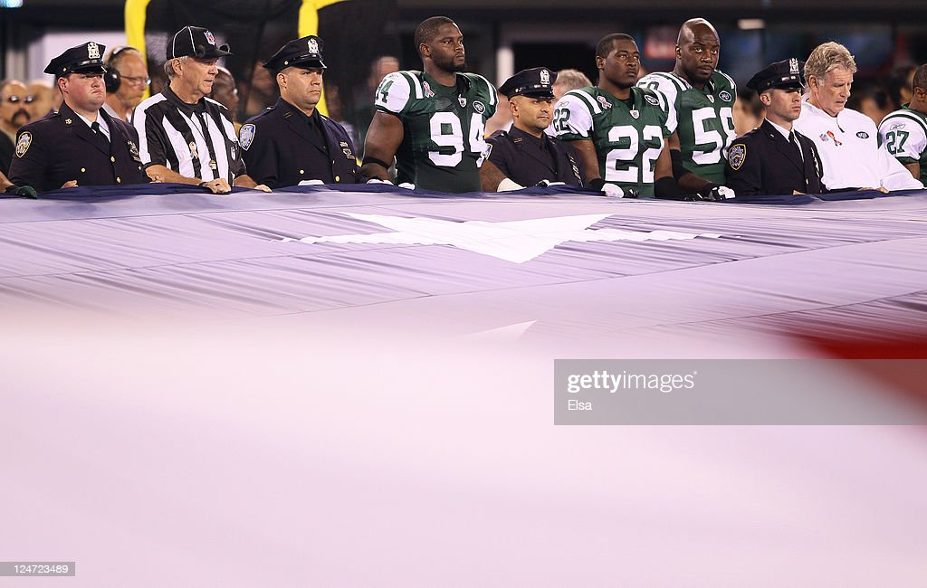 Marcus Dixon Brodney Pool and Bryan Thomas of the New York Jets stand 9/11 first responders as they American Flag on the field the performance of the...
