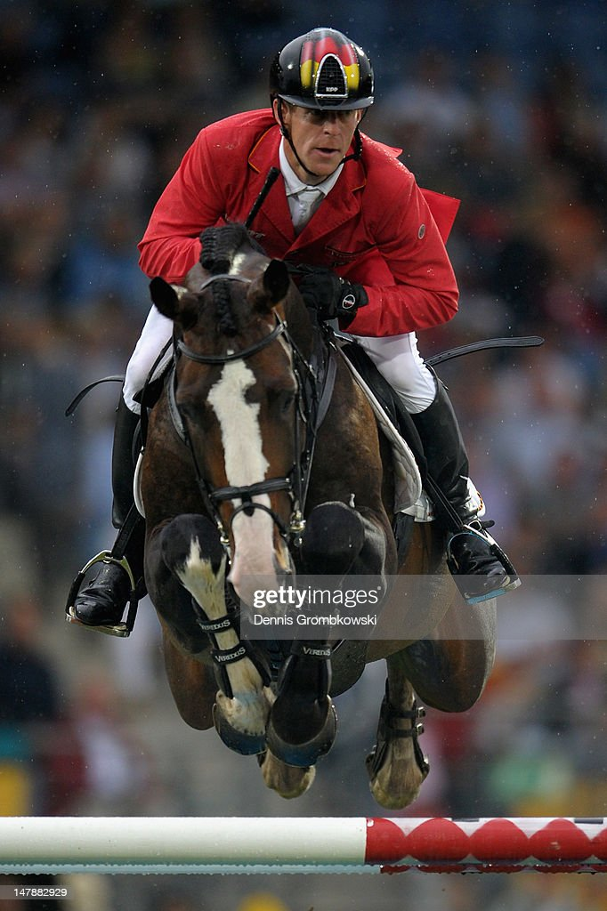 Marcus Ehning of Germany and his horse Plot Blue 2 compete in the MercedesBenz Price team jumping competition during day three of the 2012 CHIO...