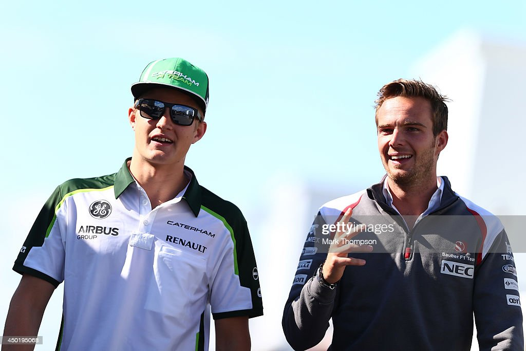 Marcus Ericsson of Sweden and Caterham and test driver Giedo Van Der Garde of Sauber walks across the paddockduring practice ahead of the Canadian...
