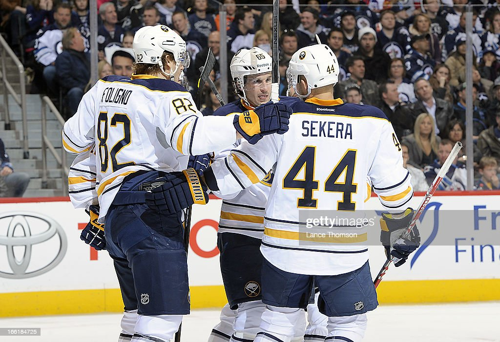 Marcus Foligno #82, Brian Flynn #65 and Andrej Sekera #44 of the Buffalo Sabres celebrate a third period goal against the Winnipeg Jets at the MTS Centre on April 9, 2013 in Winnipeg, Manitoba, Canada.