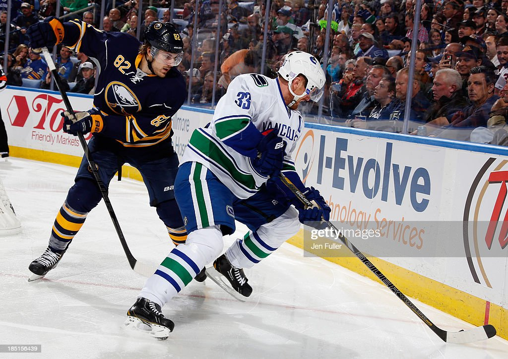 Marcus Foligno #82 of the Buffalo Sabres and Henrik Sedin #33 of the Vancouver Canucks battle for the puck along the boards at First Niagara Center on October 17, 2013 in Buffalo, New York. Vancouver defeated Buffalo 3-0.