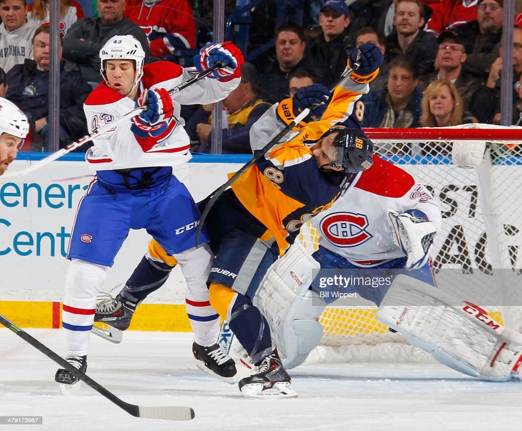 Marcus Foligno of the Buffalo Sabres gets upended by Mike Weaver of the Montreal Canadiens on March 16 2014 at the First Niagara Center in Buffalo...
