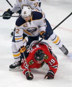Marcus Foligno of the Buffalo Sabres knocks Jonathan Toews of the Chicago Blackhawks to the ice at the United Center on October 12 2013 in Chicago...