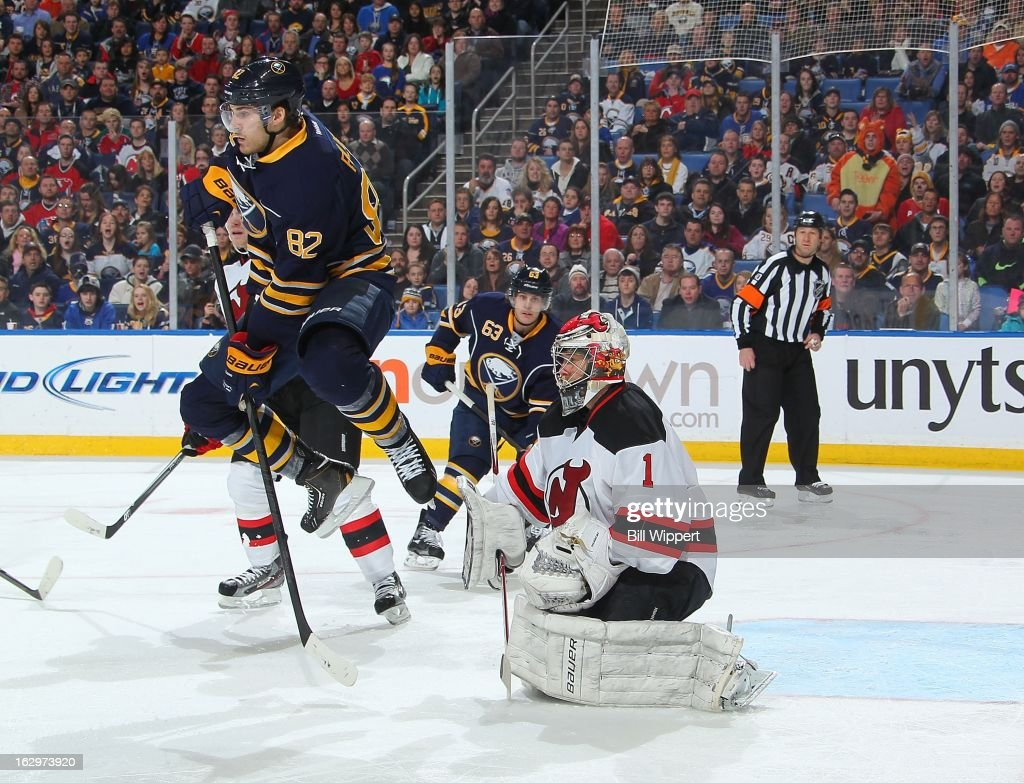 Marcus Foligno #82 of the Buffalo Sabres leaps in the air in an attempt to screen <a gi-track='captionPersonalityLinkClicked' href=/galleries/search?phrase=Johan+Hedberg&family=editorial&specificpeople=202078 ng-click='$event.stopPropagation()'>Johan Hedberg</a> #1 of the New Jersey Devils on March 2, 2013 at the First Niagara Center in Buffalo, New York.