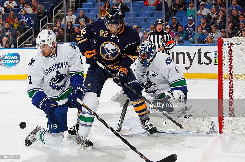 <a gi-track='captionPersonalityLinkClicked' href=/galleries/search?phrase=Marcus+Foligno&family=editorial&specificpeople=5662790 ng-click='$event.stopPropagation()'>Marcus Foligno</a> #82 of the Buffalo Sabres looks for a rebound while being defended by <a gi-track='captionPersonalityLinkClicked' href=/galleries/search?phrase=Christopher+Tanev&family=editorial&specificpeople=7228624 ng-click='$event.stopPropagation()'>Christopher Tanev</a> #8 and goalie <a gi-track='captionPersonalityLinkClicked' href=/galleries/search?phrase=Roberto+Luongo&family=editorial&specificpeople=202638 ng-click='$event.stopPropagation()'>Roberto Luongo</a> #1 of the Vancouver Canucks on October 17, 2013 at the First Niagara Center in Buffalo, New York.