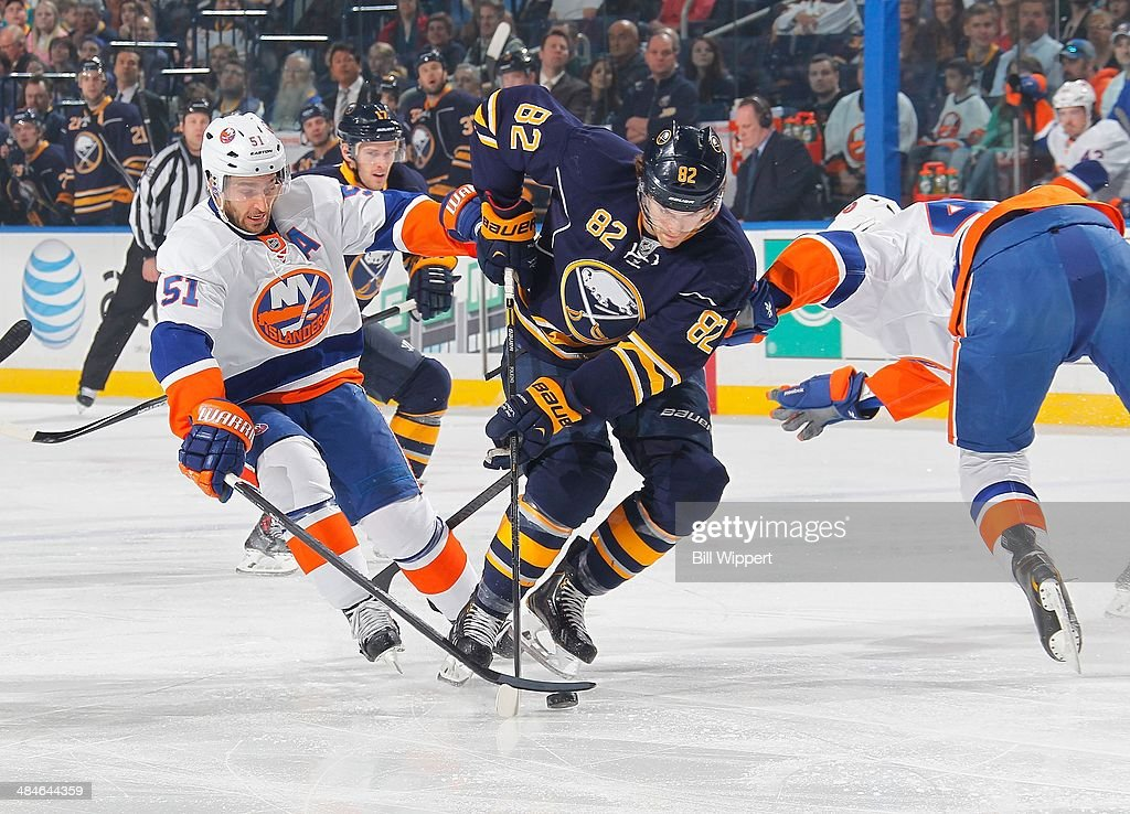 Marcus Foligno #82 of the Buffalo Sabres moves the puck against Frans Nielsen #51 of the New York Islanders on April 13, 2014 at the First Niagara Center in Buffalo, New York.