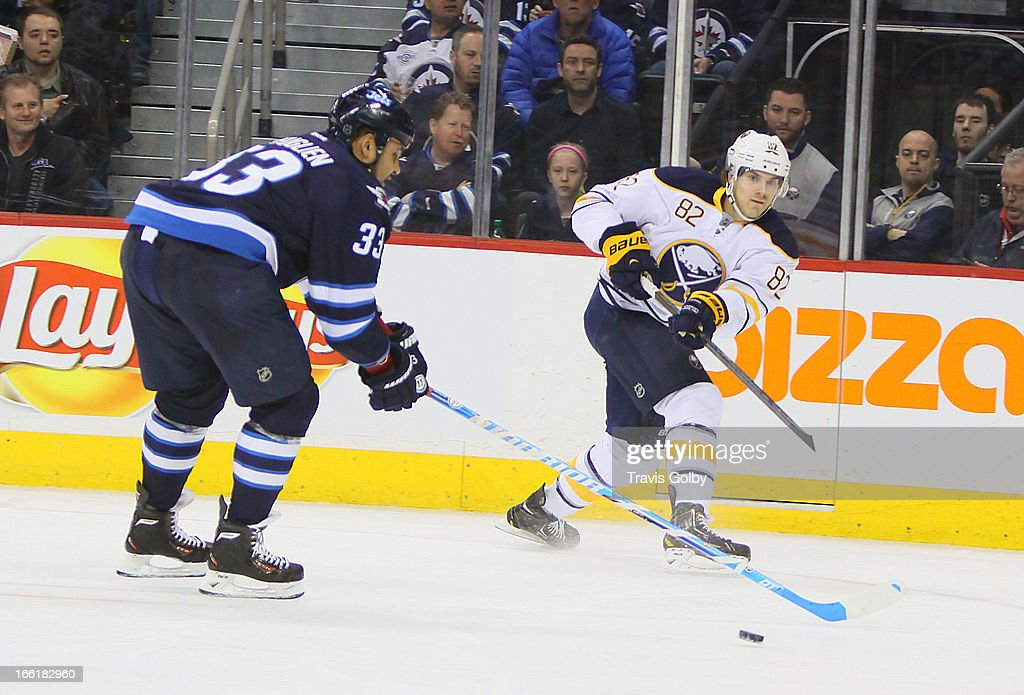 Marcus Foligno #82 of the Buffalo Sabres passes the puck as Dustin Byfuglien #33 of the Winnipeg Jets defends during second-period action at the MTS Centre on April 9, 2013 in Winnipeg, Manitoba, Canada.
