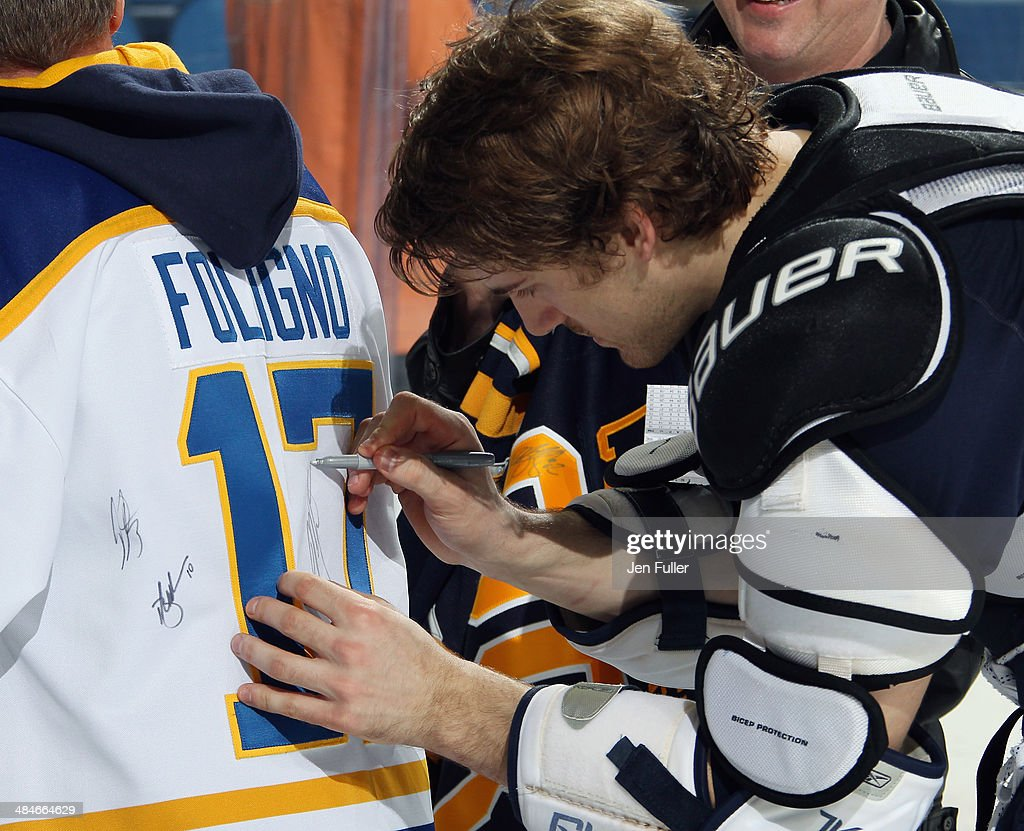<a gi-track='captionPersonalityLinkClicked' href=/galleries/search?phrase=Marcus+Foligno&family=editorial&specificpeople=5662790 ng-click='$event.stopPropagation()'>Marcus Foligno</a> #82 of the Buffalo Sabres signs the jersey of a fan after playing the New York Islanders at First Niagara Center on April 13, 2014 in Buffalo, New York. New York defeated Buffalo 4-3.