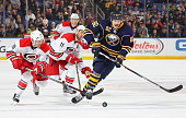 Marcus Foligno of the Buffalo Sabres skates for the puck against JohnMichael Liles of the Carolina Hurricanes during an NHL game on November 27 2015...