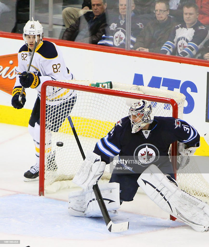 Marcus Foligno #82 of the Buffalo Sabres watches a shot by teammate Kevin Porter (not shown) slip past goaltender Ondrej Pavelec #31 of the Winnipeg Jets for a third-period goal at the MTS Centre on April 9, 2013 in Winnipeg, Manitoba, Canada.