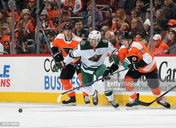 Marcus Foligno of the Minnesota Wild battles for the loose puck against Dale Weise and Jori Lehtera of the Philadelphia Flyers on November 11 2017 at...