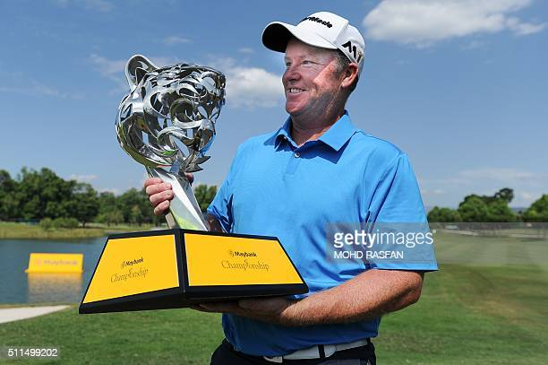 Marcus Fraser of Australia poses with the trophy after winning the 2016 Maybank Malaysia Championship golf tournament in Kuala Lumpur on February 21...