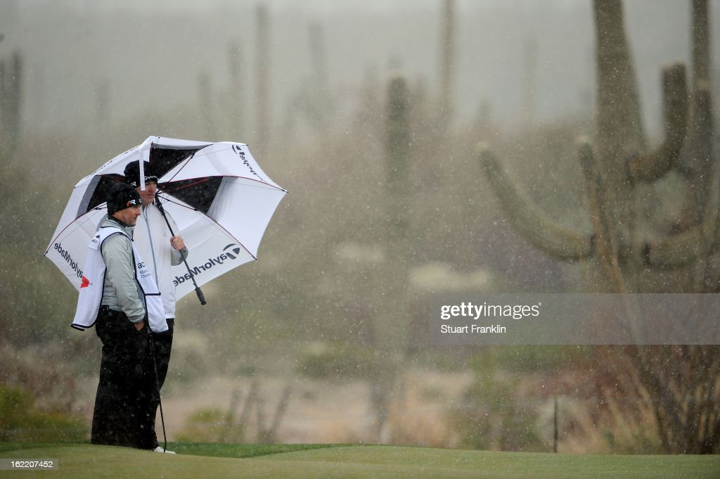 Marcus Fraser of Australia stands under an umbrella with his caddie as snow and rain fall during the first round of the World Golf Championships - Accenture Match Play at the Golf Club at Dove Mountain on February 20, 2013 in Marana, Arizona.