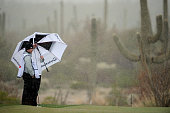 Marcus Fraser of Australia stands under an umbrella with his caddie as snow and rain fall during the first round of the World Golf Championships...