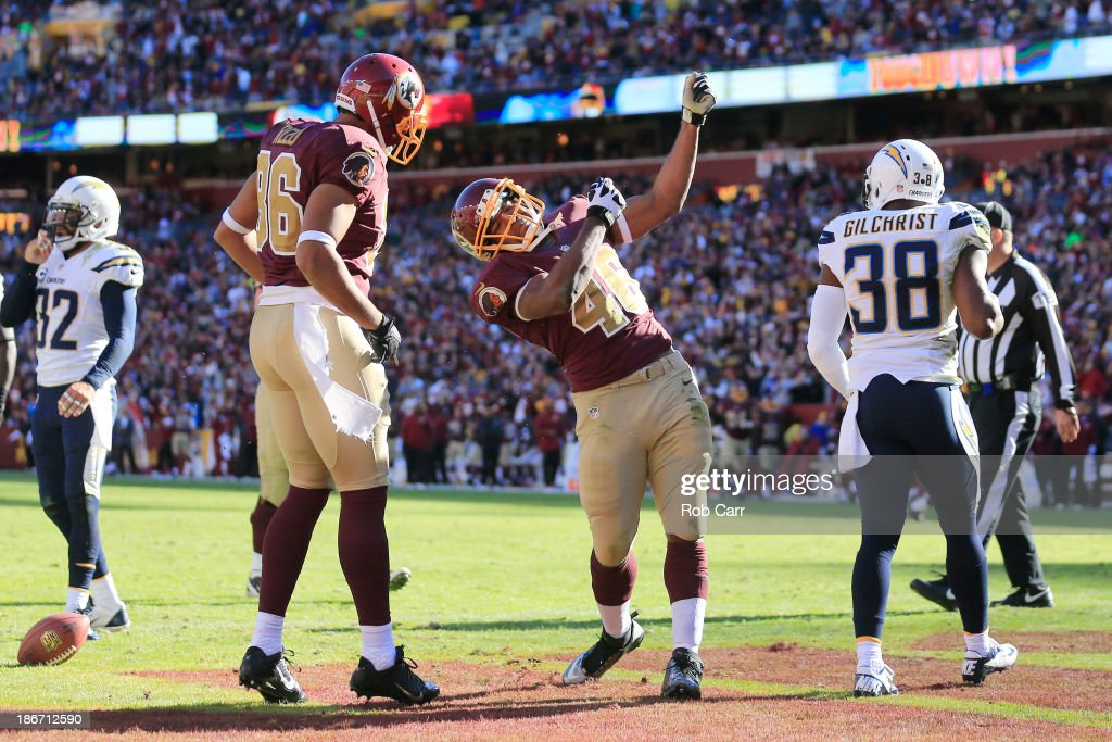 Marcus Gilchrist #38 of the San Diego Chargers looks on as running back Alfred Morris #46 of the Washington Redskins celebrates with teammate Jordan Reed #86 after rushing for a second quarter touchdown at FedExField on November 3, 2013 in Landover, Maryland.