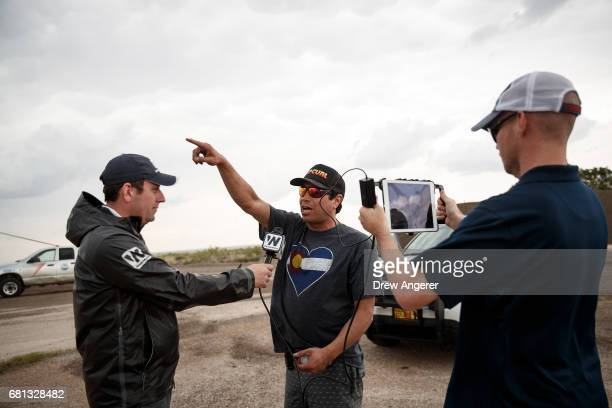 Marcus Gutierrez crew member and driver of the Doppler on Wheels vehicle is interviewed by Ben McMillan of 'Weather Nation' as they wait for a...