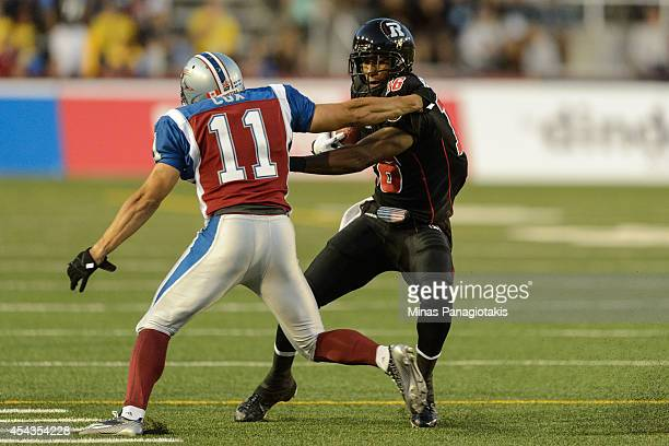 Marcus Henry of the Ottawa Redblacks shakes off Chip Cox of the Montreal Alouettes during the CFL game at Percival Molson Stadium on August 29 2014...