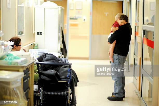 NURSE Marcus is seen being held by his dad Stephen while his mom Judy wait at the Sick Kids Emergency room to see a nurse