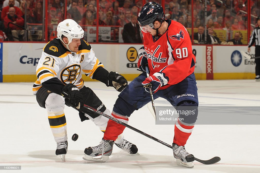 Marcus Johansson #90 of the Washington Capitals and Andrew Ference #21 of the Boston Bruins fight for the puck during Game Six of the Eastern Conference Quarterfinals of the 2012 NHL Stanley Cup Playoffs on April 22, 2012 at the Verizon Center in Washington, DC.
