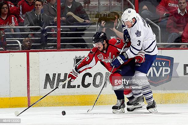 Marcus Johansson of the Washington Capitals and Dion Phaneuf of the Toronto Maple Leafs battle for the puck in the first period during an NHL game at...