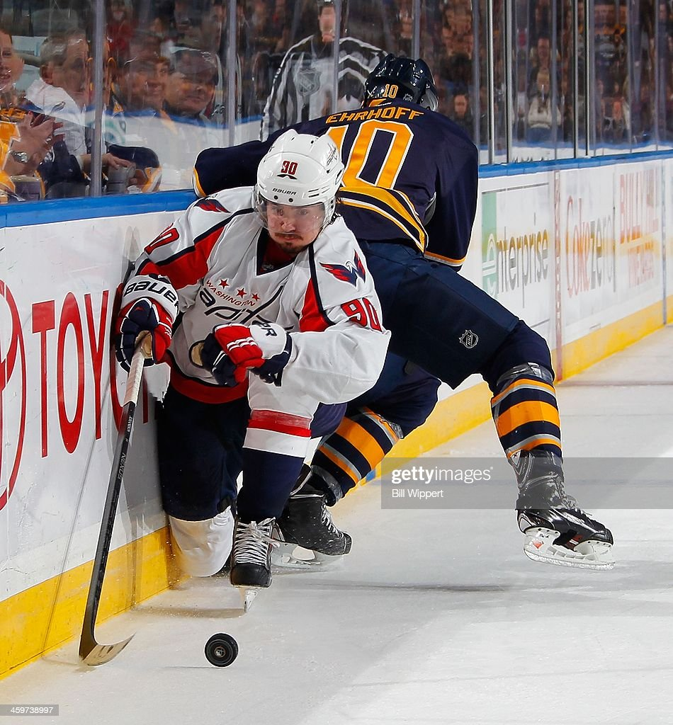 Marcus Johansson of the Washington Capitals avoids a check from Christian Ehrhoff of the Buffalo Sabres during the second period on December 29 2013...