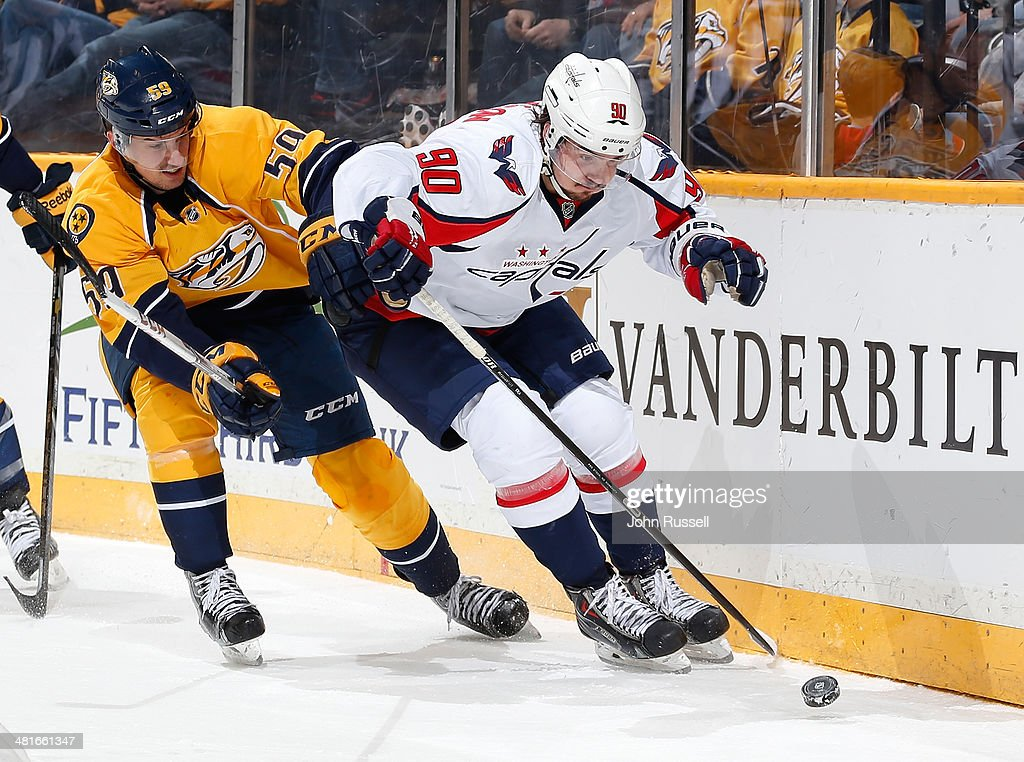 Marcus Johansson #90 of the Washington Capitals battles for the puck against Roman Josi #59 of the Nashville Predators during an NHL game at Bridgestone Arena on March 30, 2014 in Nashville, Tennessee.